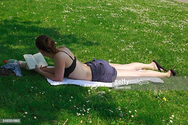 KoblenzOberwerth Kaiserin Augusta Anlagen Rhine park landscape park young woman on a lawn sunbathing and reading