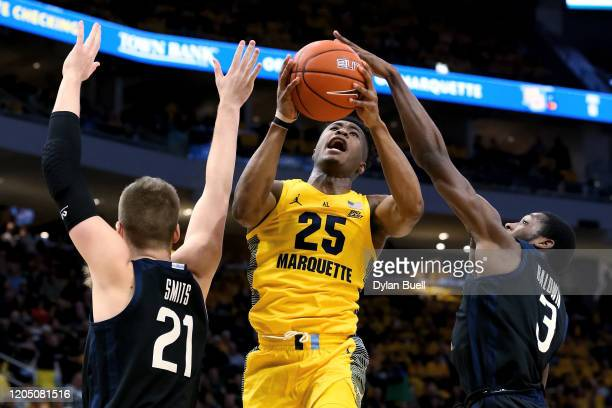 Koby McEwen of the Marquette Golden Eagles attempts a shot while being guarded by Derrik Smits and Kamar Baldwin of the Butler Bulldogs in the first...