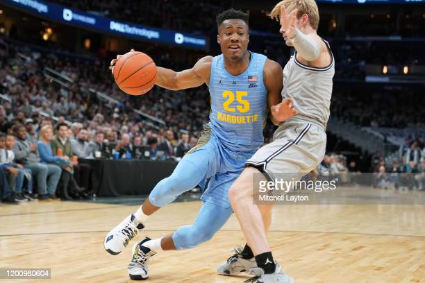 Koby McEwen of the Marquette Golden Eagles dribbles the ball by Mac McClung of the Georgetown Hoyas during a college basketball game at the Capital...