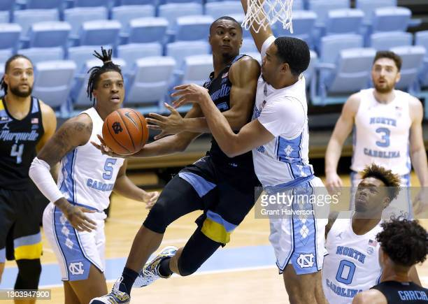 Koby McEwen of the Marquette Golden Eagles drives against Garrison Brooks of the North Carolina Tar Heels during the second half of their game at the...