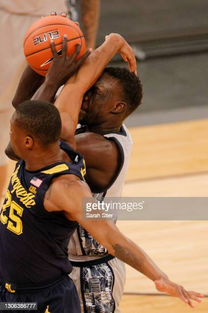 Koby McEwen of the Marquette Golden Eagles fouls Chudier Bile of the Georgetown Hoyas during the second half of their first round game of the Big...