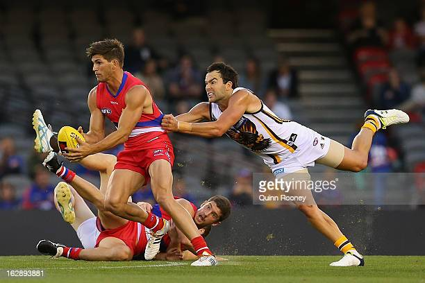 Koby Stevens of the Bulldogs handballs whilst being tackled by Jordan Lewis of the Hawks during the round two NAB Cup AFL match between the Western...