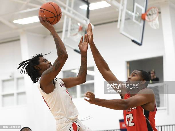 Koby Thomas of the Robert Morris Colonials puts up a shot as Alex Holcombe of the Youngstown State Penguins defends during the first half in the game...