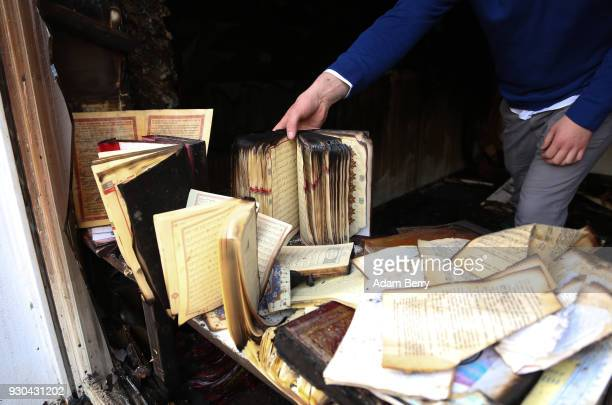 Koca Sinan Camii mosque congregation member reaches for a damaged Koran the day after a fire there the previous night on March 11 2018 in Berlin...