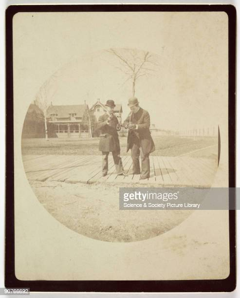 Kodak circular snapshot photograph of two smartly dressed men weraing bowler hats standing on a boardwalk taken by an unknown photographer in about...