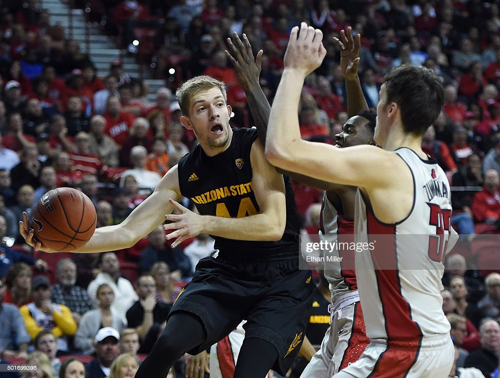 Kodi Justice #44 of the Arizona State Sun Devils passes against Dwayne Morgan #15 and Stephen Zimmerman Jr. #33 of the UNLV Rebels during their game at the Thomas & Mack Center on December 16, 2015 in Las Vegas, Nevada. Arizona State won 66-56.