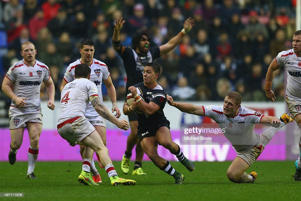 Kodi Nikorima of New Zealand evades the grasp of Tom Burgess of England during the third International Rugby League Test Series match between England and New Zealand at DW Stadium on November 14, 2015 in Wigan, England.