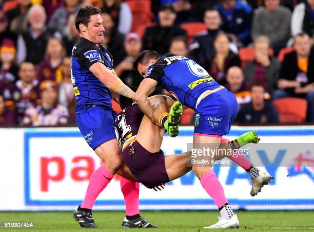 Kodi Nikorima of the Broncos is picked up in the tackle by Josh Jackson and Josh Reynolds of the Bulldogs during the round 20 NRL match between the...