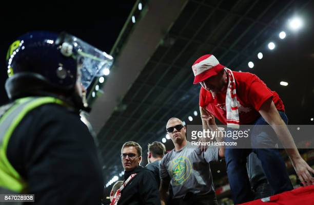 Koeln fans are monitored by police during the UEFA Europa League group H match between Arsenal FC and 1 FC Koeln at Emirates Stadium on September 14...