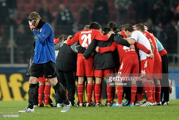 Koeln players come together while Ralf Faehrmann of Eintracht Frankfurt shows his frustration after the Bundesliga match between 1.FC Koeln and...