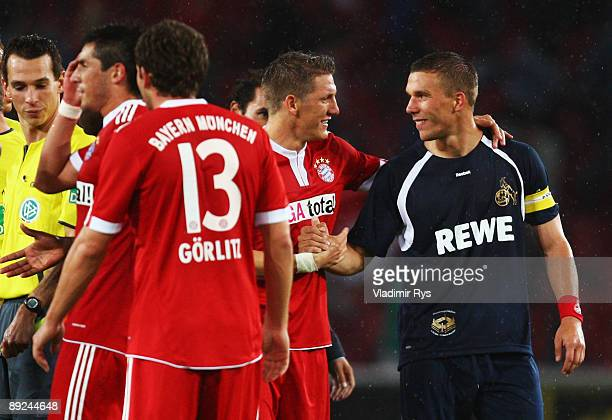 Koeln's Lukas Podolski speaks with Bastian Schweinsteiger of Bayern after the preseason friendly match between 1 FC Koeln and FC Bayern Muenchen at...