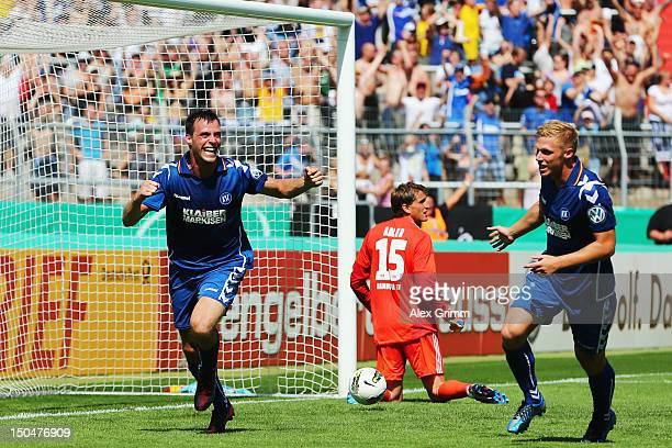 Koen van der Biezen of Karlsruhe celebrates his team's first goal with team mate Rouwen Hennings as goalkeeper Rene Adler of Hamburg reacts during...