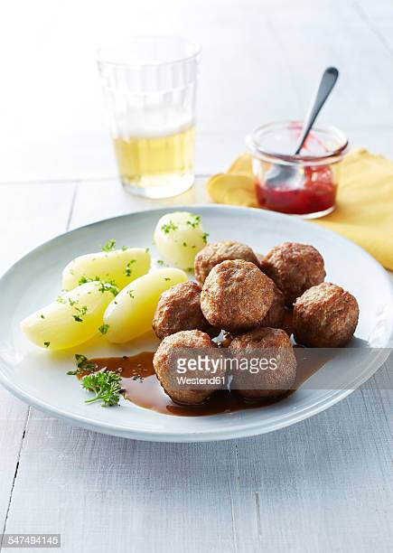 Koettbullar, Swedish meatballs with potatoes and sauce on plate, cowberries