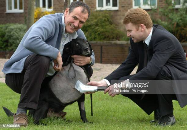 Koff a fiveyearold black Labrador from Bransgore in Dorset plays with his owner Simon Baseley and vet John Innes in Manchester following pioneering...