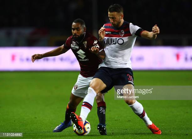 Koffi Dijdji of Torino FC competes for the ball with Mitchell Dijks of Bologna FC during the Serie A match between Torino FC and Bologna FC at Stadio...