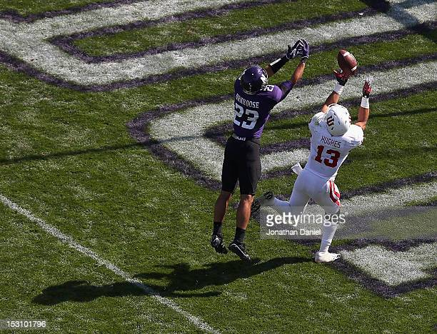 Kofi Hughes of the Indiana Hoosiers catches a touchdown pass over Nick VanHoose of the Northwestern Wildcats at Ryan Field on September 29, 2012 in...