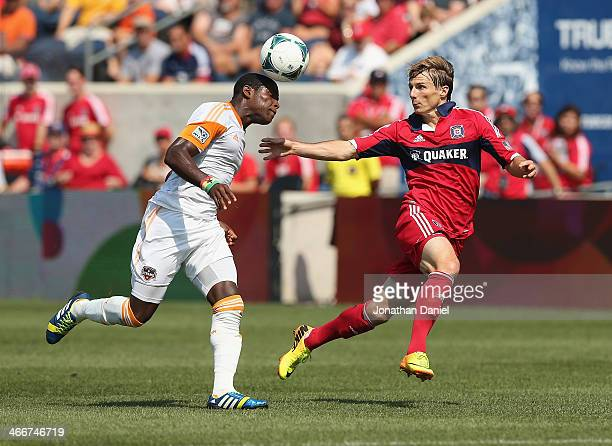 Kofi Sarkodie of the Houston Dynamo heads the ball against Chris Rolfe of the Chicago Fire during an MLS match at Toyota Park on September 1 2013 in...
