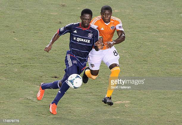 Kofi Sarkodie#8 of the Houston Dynamo battles for the ball against Patrick Nyarko of the Chicago Fire at BBVA Compass Stadium on July 27 2013 in...