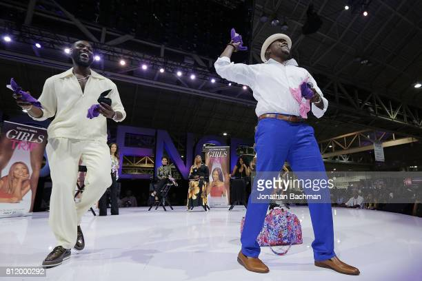 Kofi Siriboe left and Will Packer from the movie Girls Trip throw towels to the crowd during the Essence Music Festival at the Ernest N Morial...
