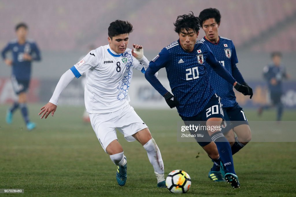 Koga Taiyo of Japan and #8 Yakhshiboev Jasurbek of Uzbekistan in action during AFC U23 Championship Quarter-final between Japan and Uzbekistan at Jiangyin Sports Center on January 19, 2018 in Jiangyin, China.