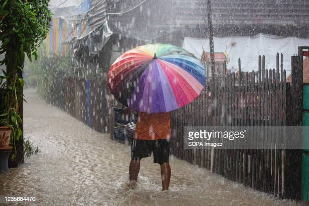 Koh Kret resident walks through a submerged alley. Twenty provinces have been affected by the Dianmu storm. Each day the riverside communities in...