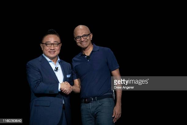 DJ Koh president and CEO of Samsung Electronics shakes hands with Satya Nadella chief executive officer of Microsoft during a launch event for the...