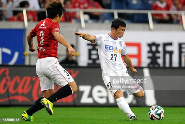 Kohei Shimizu of Sanfrecce Hiroshima and Tomoya Ugajin of Urawa Red Diamonds compete for the ball during the J. League match between Urawa Red...