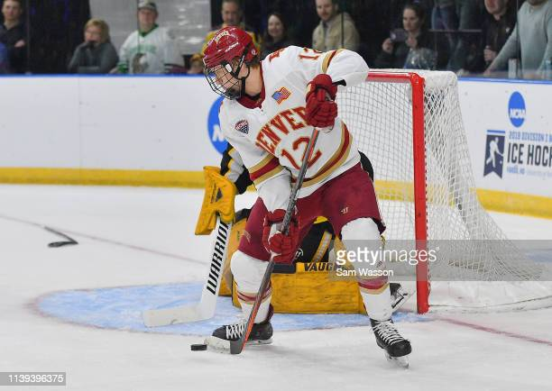 Kohen Olischefski of the Denver Pioneers controls the puck in front of the net against Zackarias Skog of the American International Yellow Jackets...
