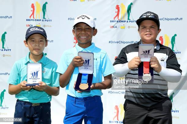 Kohki Maeda third place, Ryan Kana Tanke first place, Beau Allen second place overall in the boys 7-9 division, pose with their medals following the...