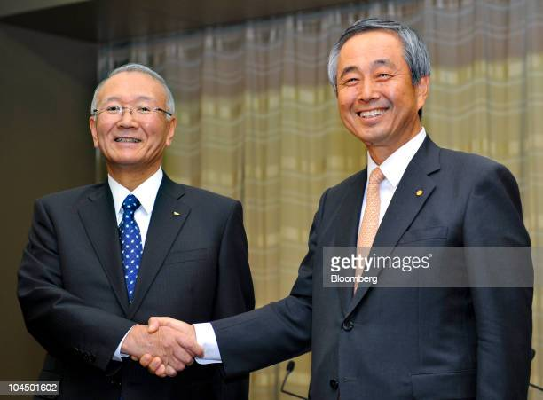 Koichi Ina president of Daihatsu Motor Co left shakes hands with Yoichiro Ichimaru executive vice president of Toyota Motor Corp during a joint news...