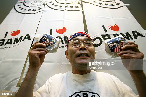 Koichi Morii employee of Obama Kaisanbutsu holds 'Obama fish burger' which is for sale in Obama City during a celebration party for the...