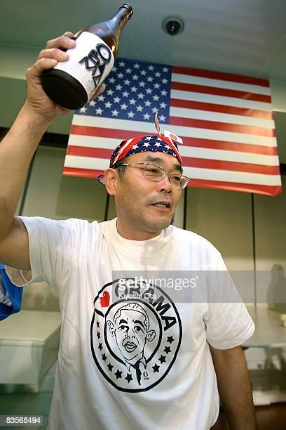 Koichi Morii employee of Obama Kaisanbutsu holds up a bottle of sake during a celebration party for the Presidentelect US Sen Barack Obama following...