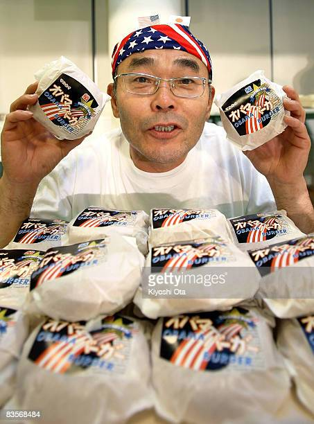 Koichi Morii employee of Obama Kaisanbutsu poses with 'Obama fish burger' which is for sale in Obama City during a celebration party for the...