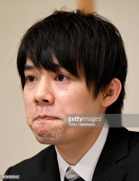 Koichiro Wada president of Japan's virtual currency exchanges Coincheck listens to questions during a press conference in Tokyo on March 8 2018 The...