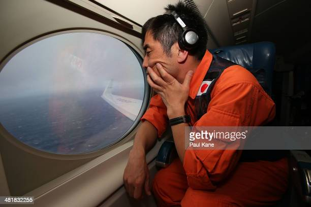 Koji Kubota of the Japan Coast Guard keeps watch for debris on board the Japan Coast Guard Gulfstream V aircraft whilst in the search zone for debris...