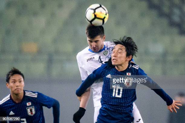 Koji Miyoshi of Japan and Akramjon Komilov of Uzbekistan compete for the ball during the AFC U23 Championship quarterfinal match between Japan and...