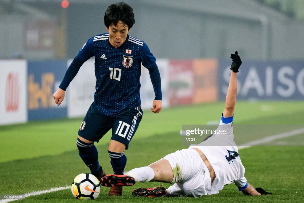 Koji Miyoshi #10 of Japan and Akramjon Komilov #4 of Uzbekistan compete for the ball during the AFC U-23 Championship quarter-final match between Japan and Uzbekistan at Jiangyin Stadium on January 19, 2018 in Jiangyin, Jiangsu Province of China.