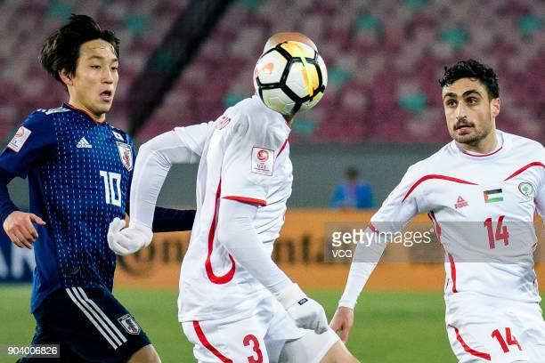 Koji Miyoshi of Japan and Mohammed Rashid of Palestine compete for the ball during the AFC U23 Championship Group B match between Japan and Palestine...