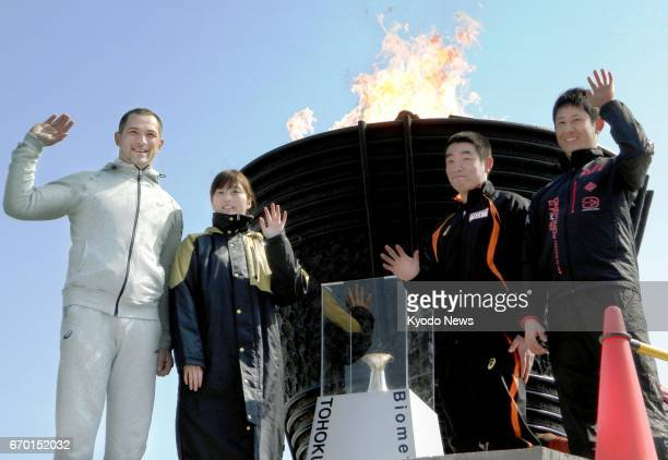 Koji Murofushi the 2004 Athens Olympic Games men's hammer throw gold medalist poses with local students in front of the borrowed 1964 Olympic...