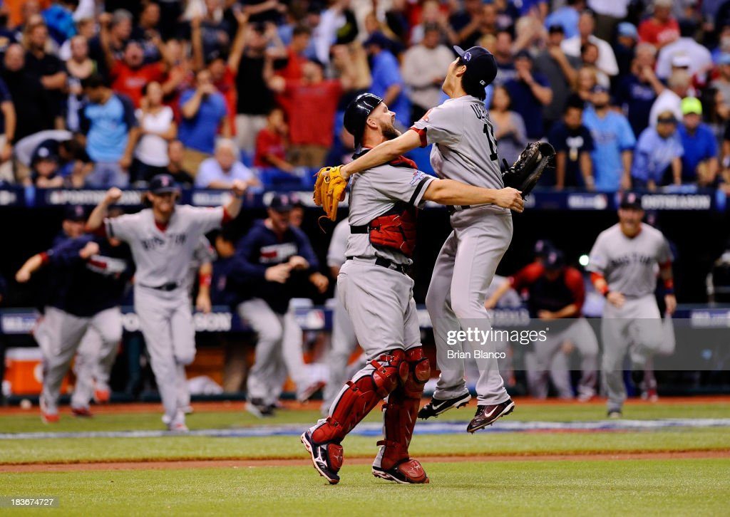 Koji Uehara #19 and David Ross #3 of the Boston Red Sox celebrate after the Boston Red Sox defeated the Tampa Bay Rays 3-1 in Game Four of the American League Division Series at Tropicana Field on October 8, 2013 in St Petersburg, Florida.