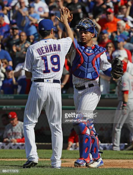 Koji Uehara and Willson Contreras of the Chicago Cubs celebrate a win against the Cincinnati Reds in the 9th inning at Wrigley Field on May 18 2017...