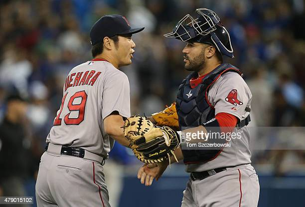 Koji Uehara of the Boston Red Sox celebrates a victory with Sandy Leon during MLB game action against the Toronto Blue Jays on June 29 2015 at Rogers...