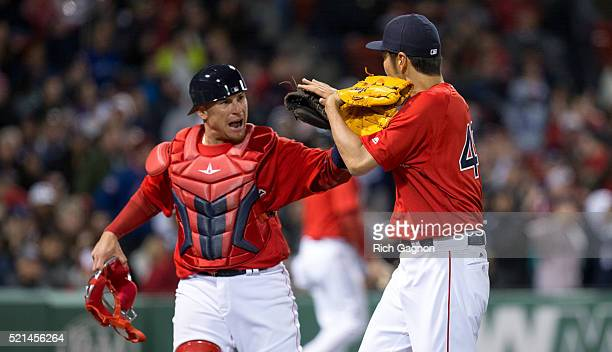 Koji Uehara of the Boston Red Sox celebrates the third out of the inning with teammate Christian Vazquez during the eighth inning against the Toronto...