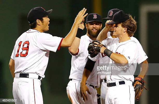 Koji Uehara of the Boston Red Sox celebrates with Mike Napoli and Brock Holt after defeating the Kansas City Royals 21 at Fenway Park on July 19 2014...