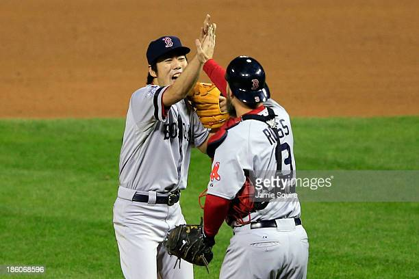Koji Uehara of the Boston Red Sox celebrates with teammate David Ross after throwing out Kolten Wong of the St Louis Cardinals to win Game Four of...