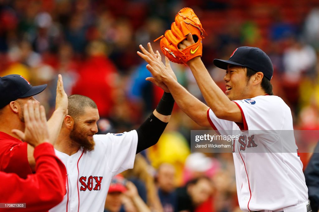Koji Uehara #19 of the Boston Red Sox celebrates with teammates after getting out of the eighth inning against the Tampa Bay Rays during the game on June 18, 2013 at Fenway Park in Boston, Massachusetts.