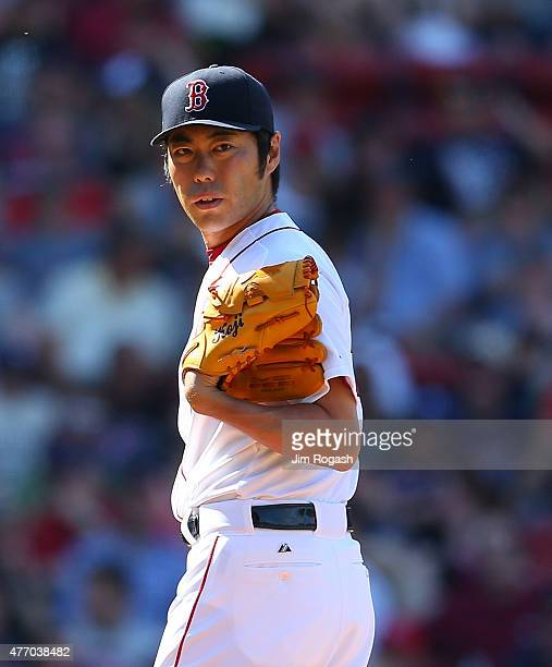 Koji Uehara of the Boston Red Sox checks the runner at first base in the ninth inning against the Toronto Blue Jaysat Fenway Park on June 13 2015 in...