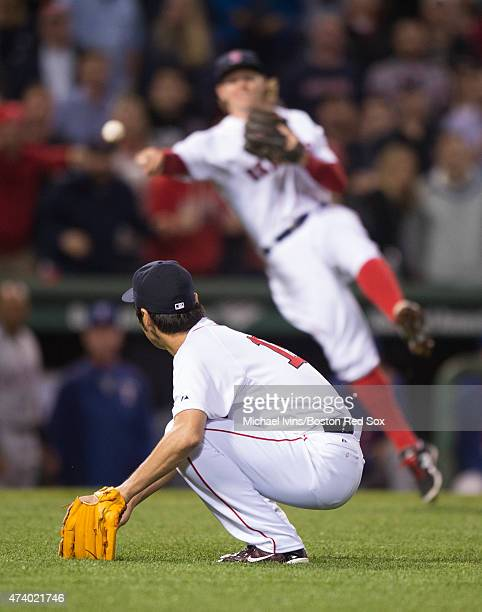 Koji Uehara of the Boston Red Sox ducks to avoid a throw to first base by Brock Holt during the ninth inning against the Texas Rangers at Fenway Park...