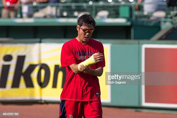 Koji Uehara of the Boston Red Sox holds his right wrist which is in a cast before a game against the Cleveland Indians on August 17 2015 in Boston...