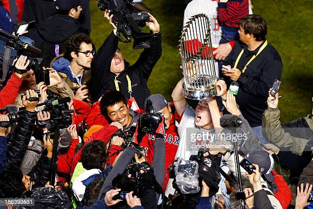 Koji Uehara of the Boston Red Sox holds up the World Series Trophy after defeating the St Louis Cardinals 61 in Game Six of the 2013 World Series at...